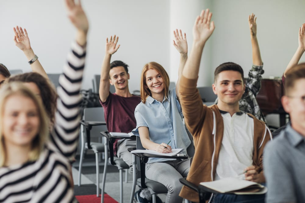 Happy students raising hands to answer a question in class.